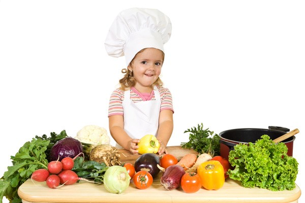 Happy little girl as a chef preparing vegetables for cooking - isolated